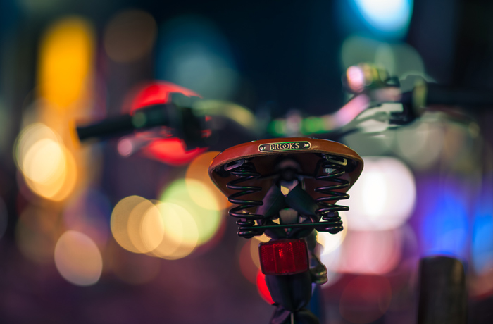 A bicycle with a Brooks saddle among a sea of brightly colored bokeh in Times Square, Manhattan