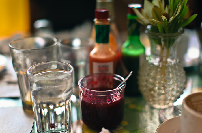 Jar of raspberry preserves among glasses and condiments at Mama's