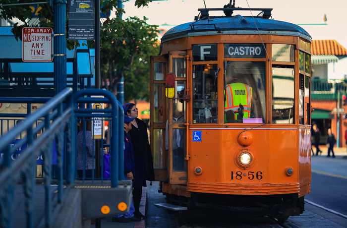 Pedestrians inquiring a driver of one of the many brightly painted historic streetcars in Fisherman's Wharf