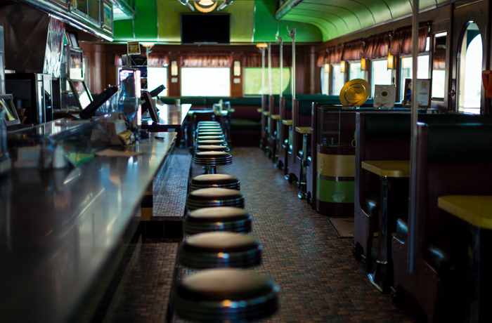 The interior of the diner include cozy table seating and a long row of stools along the 40-foot counter of green Italian marble