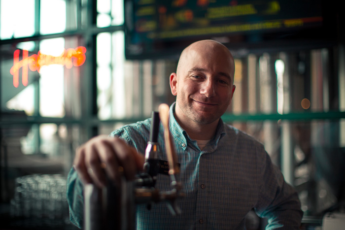 General Manager Brock Blonquist smiles as he stands behind the counter ready to pour another glass