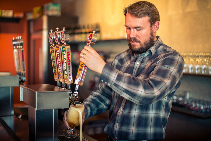 Head Brewer Kevin Ely of Uinta Brewing Company pouring a glass of Hyve Organic Honey Ale